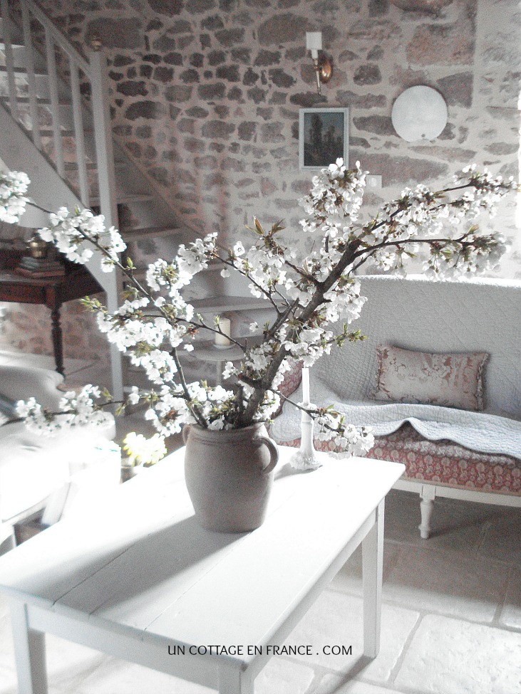 Bouquet de fleurs de cerisiers sur la table du salon du cottage