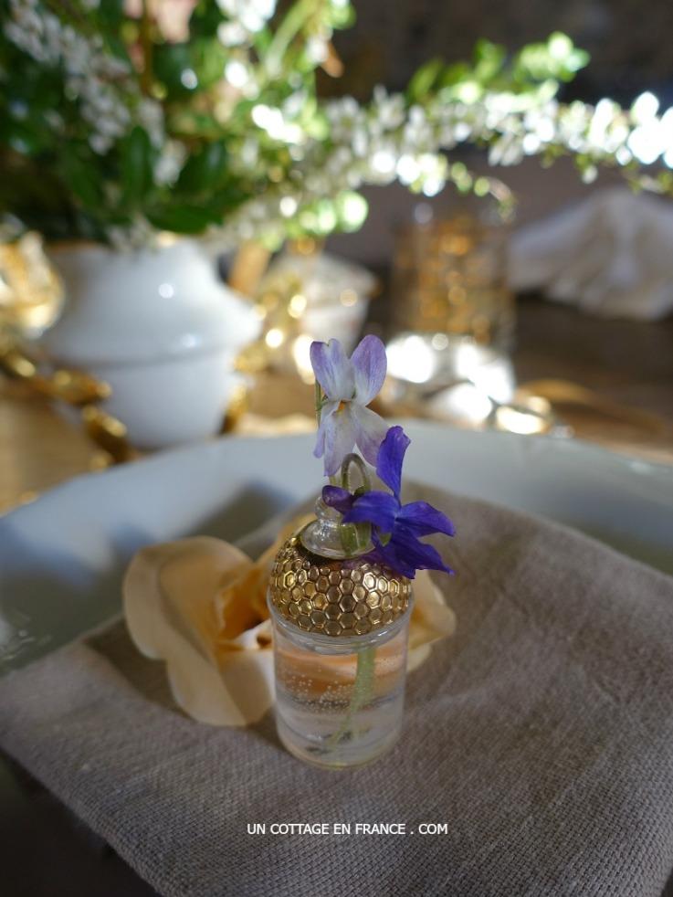 Violettes dans des bouteilles de parfum (Violets in perfume bottles as table arrangement)